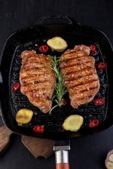 Gegrilde varkenslapje vlees in grillpan met rozemarijn, peper spaanse peper en gember op een houten bord.