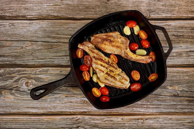 Gegrilde varkenslapje vlees in ijzerkoekepan op houten
