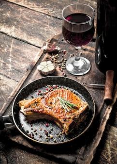 Gegrilde varkenslapje vlees met rode wijn. op houten achtergrond.