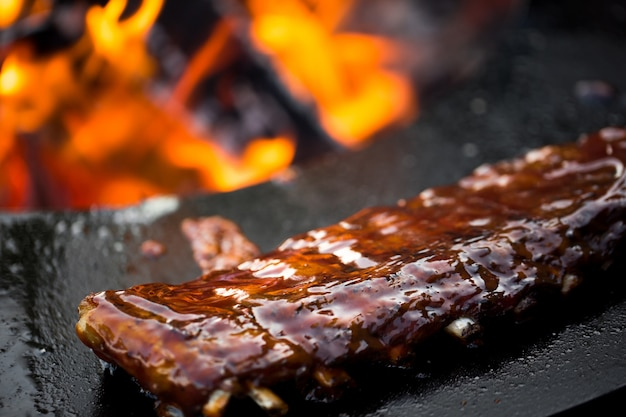Gegrilde varkensribbetjes met barbecuesaus op de grill. festival straatvoedsel