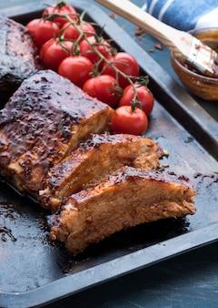 Gegrilde varkensribbetjes met gebakken cherrytomaatjes op een dienblad. gebakken vlees