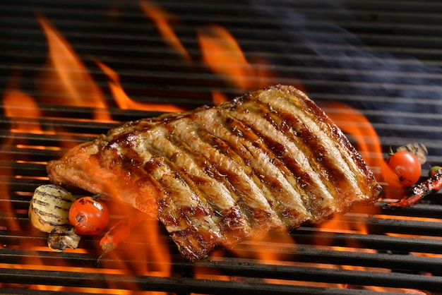 Gegrilde varkensribbetjes met groente op de vlammende grill