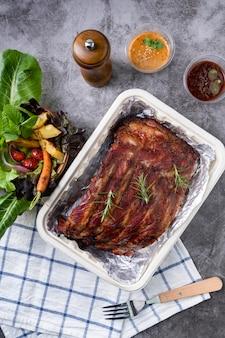 Gegrilde varkensribbetjes met groenten en sauzen op een drak tafel