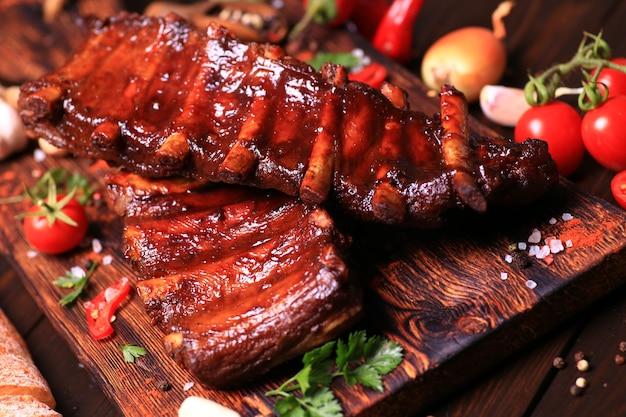 Gegrilde varkensribbetjes met kruiden en groenten op een houten ondergrond