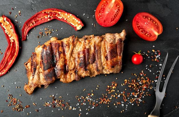 Gegrilde varkensribbetjes op een zwart bord, verse rode tomaten