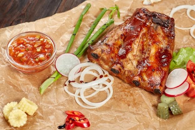 Gegrilde varkensribbetjes, zoetzure saus. vlees met groenten