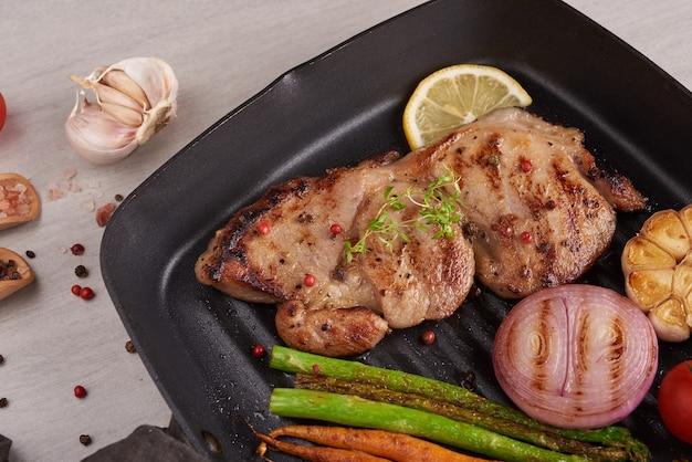 Gegrilde varkenssteak van een zomerse bbq geserveerd met groenten, asperges, worteltjes, verse tomaten en kruiden. gegrilde steak op grillpan op stenen oppervlak. bovenaanzicht.