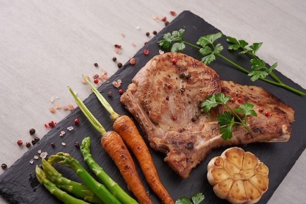 Gegrilde varkenssteak van een zomerse bbq geserveerd met groenten, asperges, worteltjes, verse tomaten en kruiden. gegrilde steak op zwarte leisteen op stenen oppervlak. bovenaanzicht.