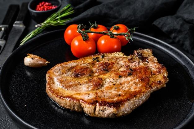 Gegrilde varkensvlees steak op bot met tomaten. zwarte achtergrond. bovenaanzicht