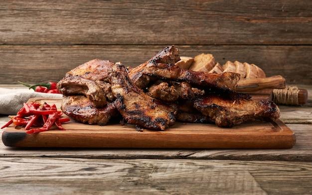Gegrilde varkensvlees steaks op het bot op een keuken snijplank en rode chili peper