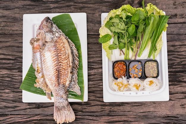 Gegrilde vis met bijgerechten op houten tafel