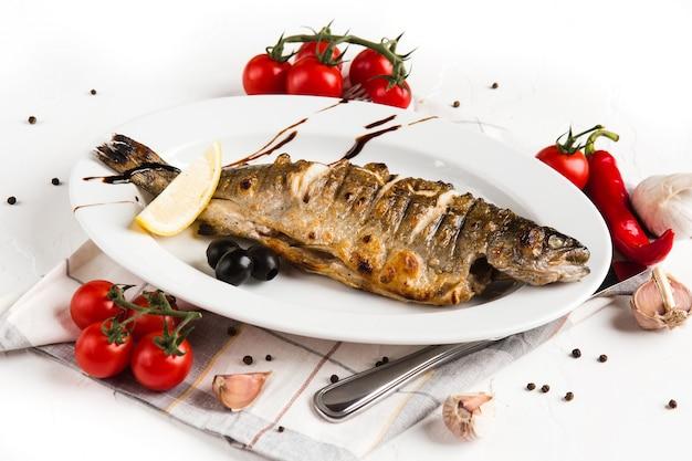 Gegrilde vis met groenten op een witte plaat