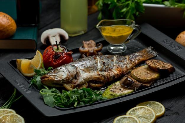 Gegrilde visbarbecue met groenten en dipsaus