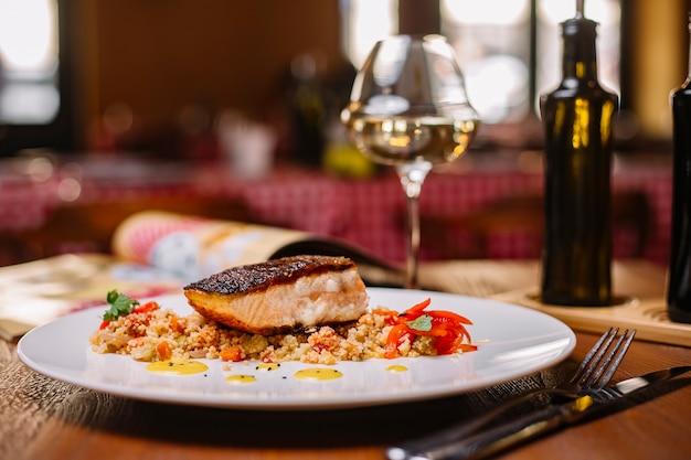 Gegrilde visfilet geserveerd bovenop de couscous salade met paprika