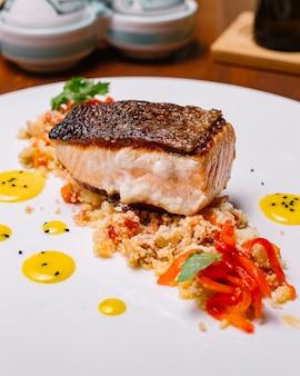 Gegrilde visfilet geserveerd bovenop de kouskoussalade met paprika verticaal