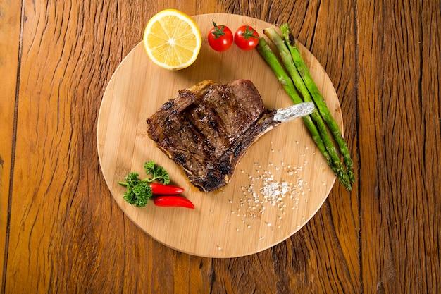 Gegrilde vleesribben op een witte plaat met tomaten bieslook en donkere hete saus aan boord