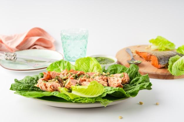 Gegrilde wilde zalm en slaschotel met groene pesto, linnen, bestek, bord, glas water