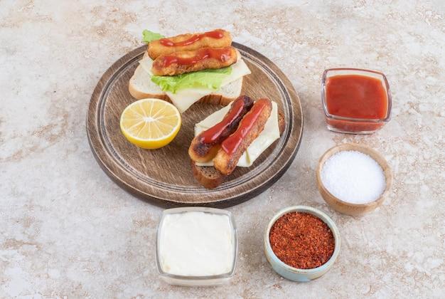 Gegrilde worst en kipnuggets op sandwich toastjes met kruiden en specerijen op een houten schotel.
