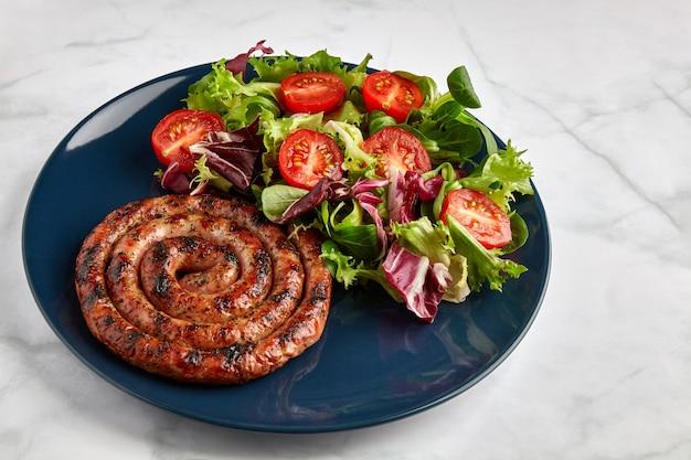 Gegrilde worst met gehakte tomaten en kruiden op een blauw bord op een lichte tafel