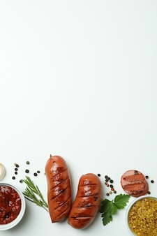 Gegrilde worst, sauzen en kruiden op witte achtergrond