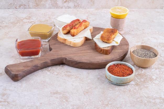 Gegrilde worstjes en kipnuggets op een broodje toast geserveerd met sauzen.