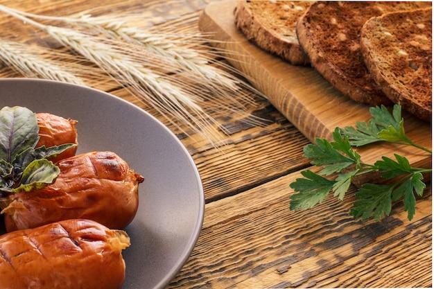 Gegrilde worstjes met groene basilicum op plaat en toast op houten snijplank met aartjes van tarwe en peterselie bladeren. bovenaanzicht.