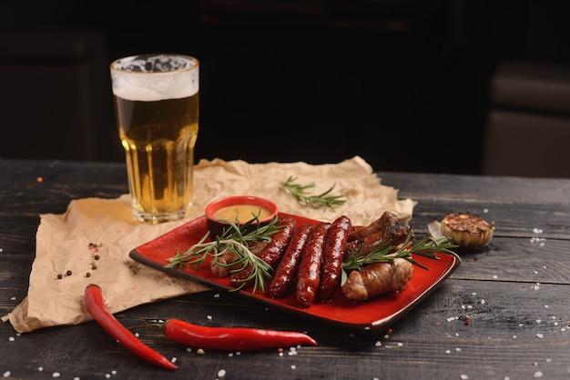 Gegrilde worstjes met rozemarijn en mosterdsaus. in een rode plaat op een houten tafel