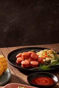 Gegrilde worstjes met sausketchup op een houten tafel