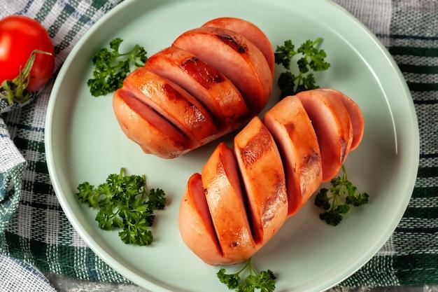 Gegrilde worstjes met verse groenten staan op de schaal