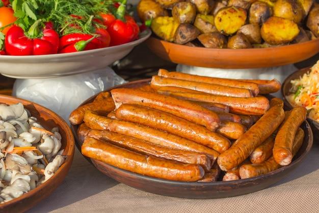 Gegrilde worstjes op een bord, gebakken aardappelen en rode paprika op tafel