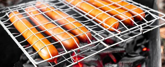 Gegrilde worstjes op grill met rook en vlam op een bos. rustieke worst aan de paal-worstjes worden gebakken boven een open vuur in het bos - campingvoedsel