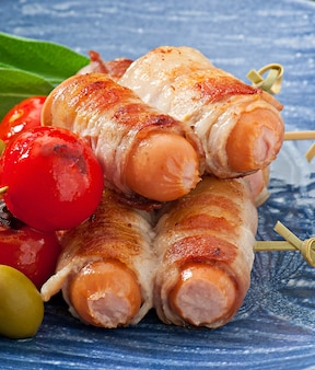 Gegrilde worstjes verpakt in reepjes spek met tomaten en salieblaadjes