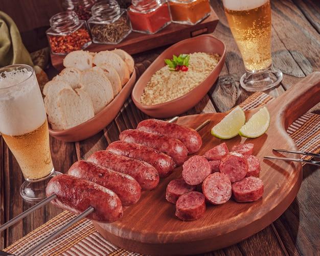 Gegrilde worstspies op een houten bord met bier, brood en farofa braziliaanse barbecue