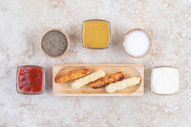 Gegrilde worststicks met selectie van sauzen opzij.