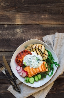 Gegrilde zalm, aubergines en tomaten met quinoa en tzatzikisaus op rustieke houten achtergrond. gezond diner. bovenaanzicht. kopieer de ruimte.