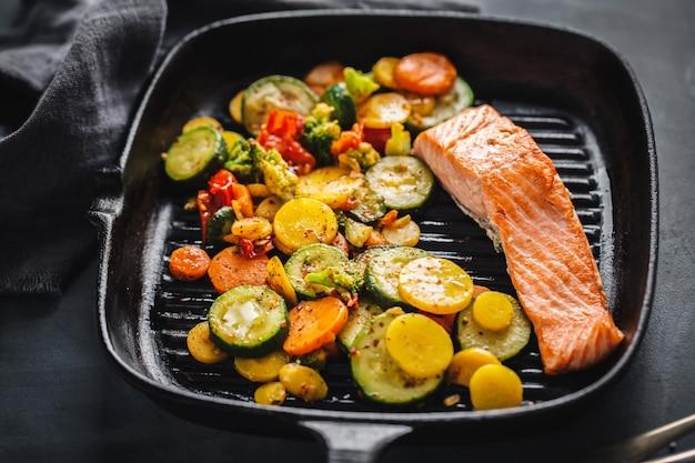 Gegrilde zalm met groenten op pan