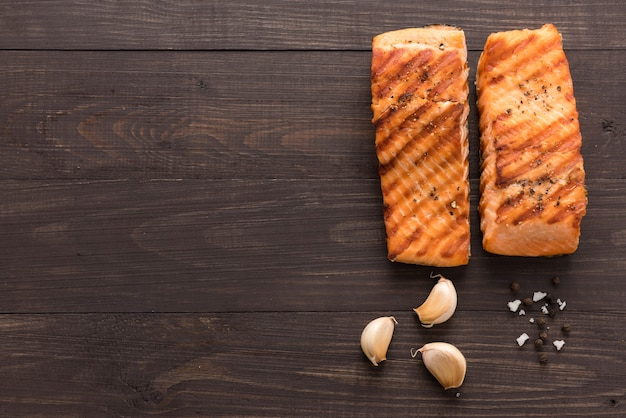 Gegrilde zalm met knoflook, peper, zout op houten achtergrond.