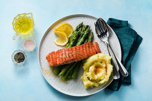 Gegrilde zalm met verse asperges en aardappelpuree op een bord. gezonde voeding op tafel