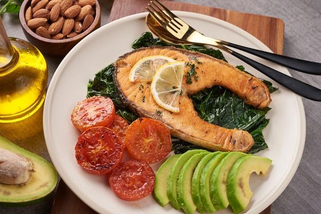 Gegrilde zalm visfilet en verse groene sla groente tomatensalade met avocado guacamole. evenwichtig voedingsconcept voor schoon eten flexitarisch mediterraan dieet.