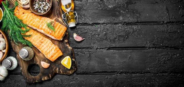 Gegrilde zalmfilet met kruiden en dille takken op donkere rustieke tafel.
