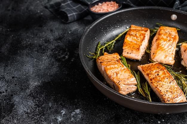 Gegrilde zalmfilet steak in een pan. zwarte achtergrond. bovenaanzicht. ruimte kopiëren.