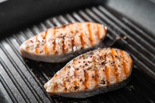 Gegrilde zalmvissen op pan op de vlammende grill.