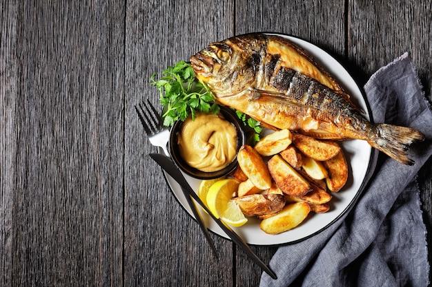 Gegrilde zeebrasem, orata, dorado-vis geserveerd op een bord met geroosterde aardappelen en mosterd, horizontaal uitzicht van bovenaf, plat gelegd, vrije ruimte
