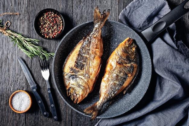 Gegrilde zeebrasem, orata, dorado-vis in een koekenpan op een donkere houten tafel met een vork, rozemarijn en peperkorrel, horizontaal uitzicht van bovenaf, plat gelegd