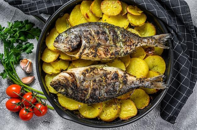Gegrilde zeebrasemvissen met aardappelen in een pan