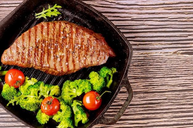 Gegrilde zeldzame biefstuk met broccoli en tomaat op de grill pan.