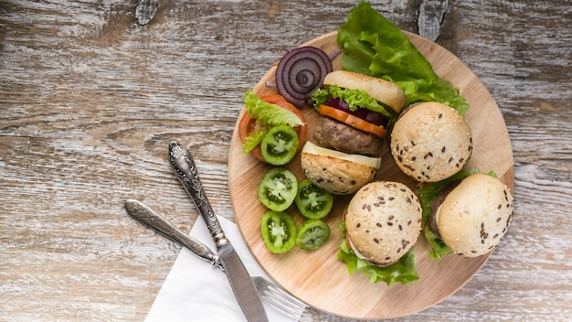 Gegrilde zelfgemaakte hamburgers met rundvlees, tomaten, kaas, zoete uien en groene salade.