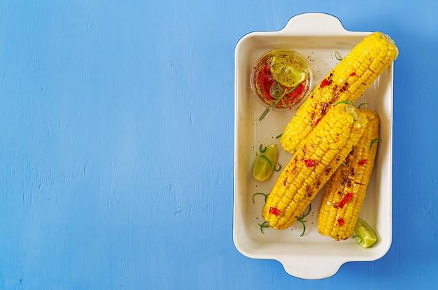 Gegrilde zoete maïs met mexicaanse saus, chili en limoen op blauwe achtergrond.