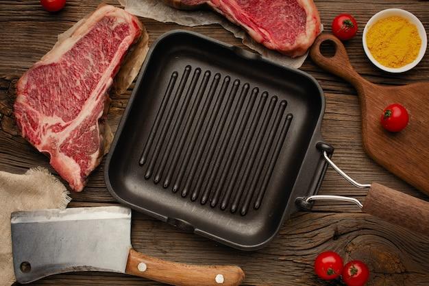 Gegrilde zwarte pan met rauw vlees steak, cherrytomaat, kruiden. bovenaanzicht met ruimte voor een inscriptie