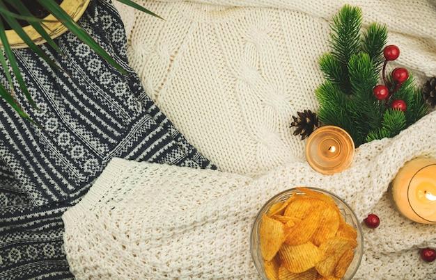 Gegroefde aardappelchips in transparante kom op gezellige achtergrond, trui, winterdecoratie, compositie met kopieerruimte. hoge kwaliteit foto